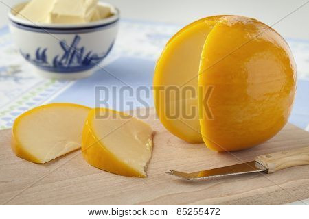 Yellow round Edam cheese with slices on a cutting board