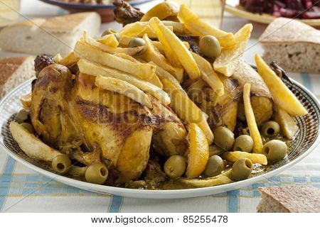 Traditional moroccan stuffed chicken with french fries, olives and preserved lemon