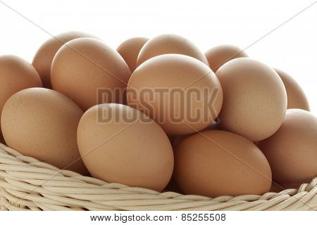 Basket with fresh brown eggs close up