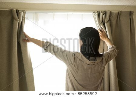 The woman who opens a curtain