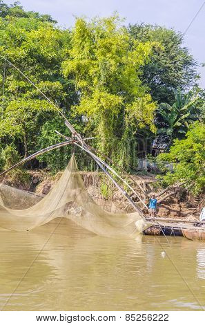 CHAU DOC, VIETNAM - JANUARY 2, 2013: Rural life in Mekong delta - Local fisherman  fishes in Bassac river using a traditional fishing net