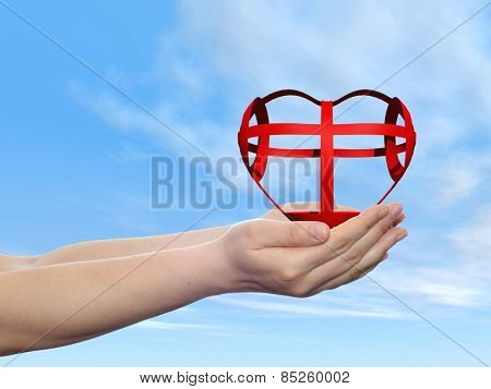 Concept or conceptual 3D red glass heart sign or symbol held in hands by a woman or child over a nice blue sky background