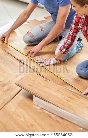 repair, building, flooring and people concept - happy couple with ruler measuring parquet board at home