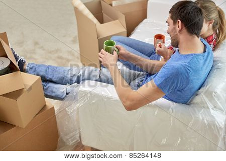 moving, home, repair and people concept - happy couple relaxing and sitting on sofa with cups in new apartment