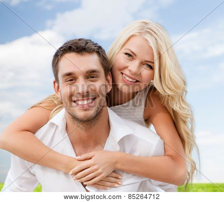 summer holiday, vacation, dating and love concept - happy couple having fun over blue sky and grass background