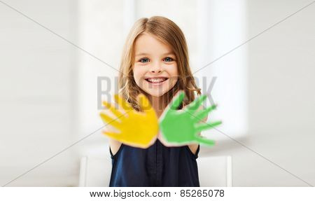 education, school, art and happiness concept - little student girl showing hands in yellow and green color at school