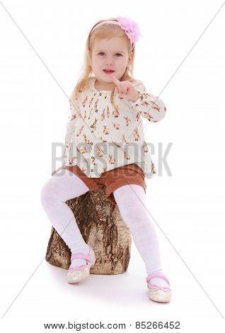 elegant beautiful girl newspaper forefinger sitting on a stump