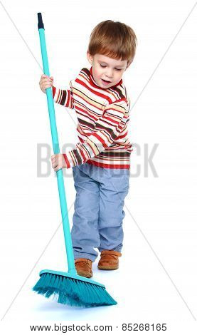 cheerful little boy sweeping the floor with a brush