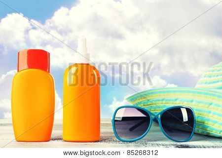 Bottles of suntan cream with sunglasses and hat on table isolated on white