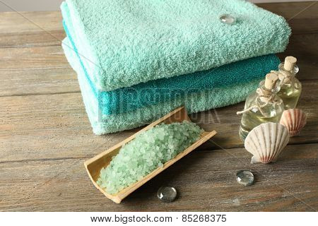 Spa composition with towels and sea salt on wooden table