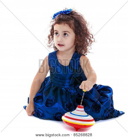 cute little girl sitting on the floor and playing dreidel