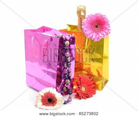 Gift Packs with a champagne bottle, necklace and flowers gerbera