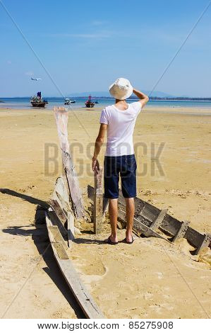 Young stranger standing on the shattered boat
