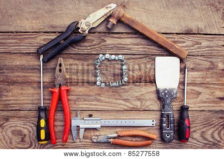 Construction tools in the form of house on wooden background.