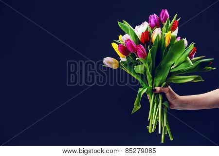 Woman's Hand Gives A Bouquet Of Tulips
