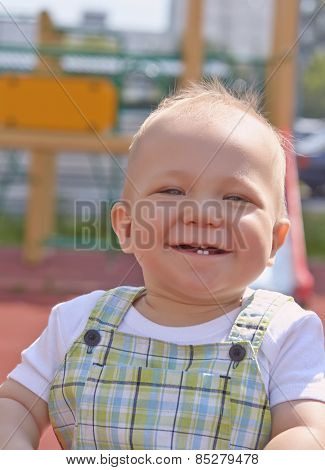Adorable little boy having fun on a swing outdoor