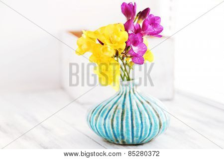 Colorful beautiful freesias on wooden windowsill