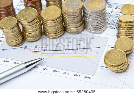 Columns Of Coins And Pen On Business Chart