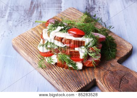 Sandwich with sausage, tomato and mayonnaise on cutting board on color wooden table background