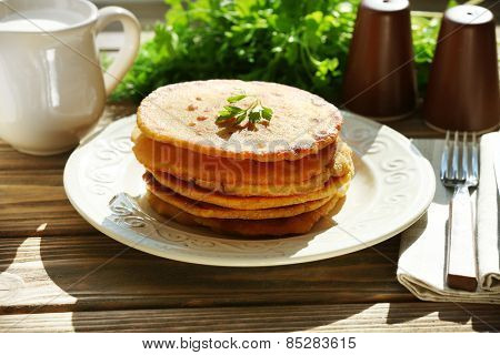 Stack of corn tortillas with stuffing and greens on wooden table background