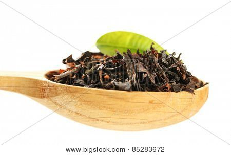 Wooden spoon with black tea with leaf isolated on white