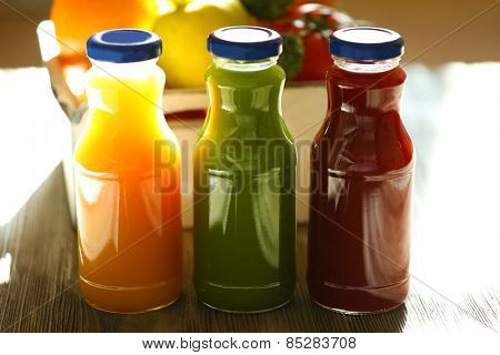 Bottles of juice with fruits and vegetables on table close up