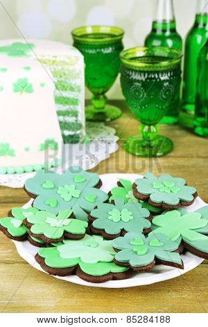 Still life with sliced cake, cookies and green beer for Saint Patrick's Day on wooden table and blurred background