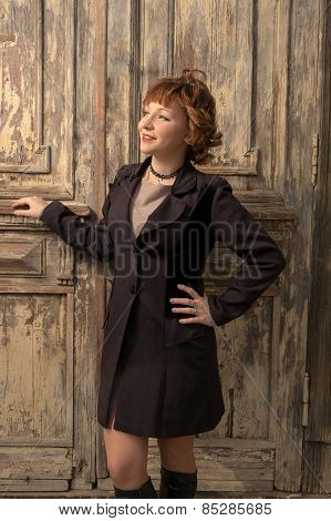 Happy sensual emotive portrait of retro woman posing near obsolete slum house door