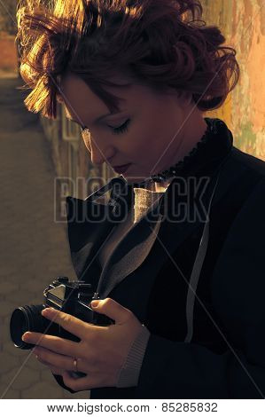 Outdoor fall lifestyle portrait of pretty young redhead woman in the city in evening backlit with ca