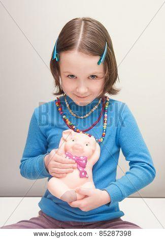 Girl Child Holding A Piggy Bank