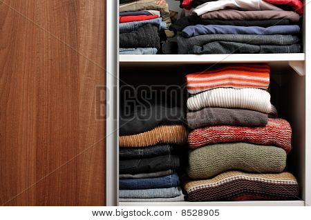 Open wardrobe with lots of folded clothes