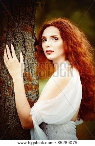 Closeup Portrait Of A Beautiful Ginger Woman Near The Tree
