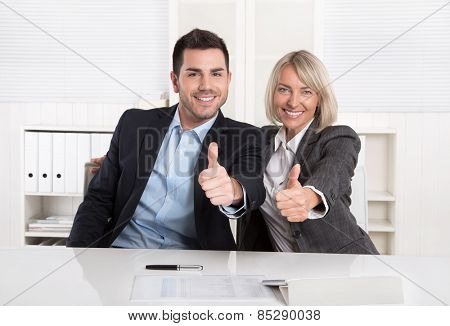 Successful business team or happy businesspeople making recommendation gesture.