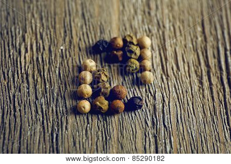 Allspice pepper on rustic wooden table background
