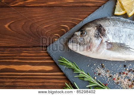 Raw dorado on the slate tray with herbs