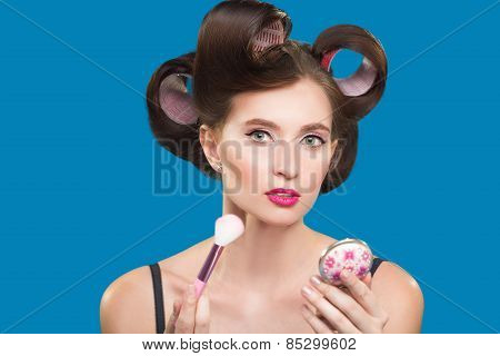 female in curlers applying rouge. makeup brush.