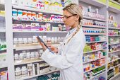 pic of concentration  - Concentrated student using tablet pc in the pharmacy - JPG