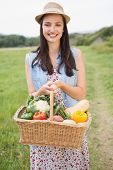 Pretty woman with basket of veg on a sunny day poster