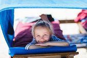 stock photo of cabana  - Little girl at luxury resort relaxing at beach cabana - JPG