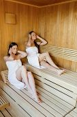 picture of sauna woman  - Young women relaxing on wooden bench at the sauna - JPG