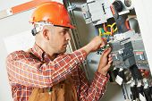 foto of fuse-box  - electrician builder engineer screwing equipment in fuse box - JPG