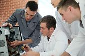 stock photo of teachers  - Students in computing class with teacher fixing hardware - JPG