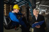 image of forklift driver  - Forklift driver talking with his manager in a large warehouse - JPG