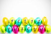 stock photo of pasqua  - feliz pasqua against colourful foil wrapped easter eggs - JPG