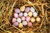pic of easter candy  - happy easter against little candy easter eggs in straw - JPG