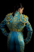 stock photo of bullfighting  - Woman bullfighter suit with blue lights on a black background - JPG