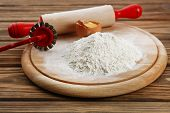 foto of plunger  - Heap of flour on cutting board with egg and plunger on wooden table - JPG