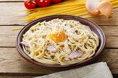 picture of carbonara  - pasta carbonara on a plate with egg yolk and parmesan cheese