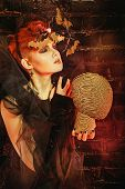 foto of witch  - Halloween witch with an unusual makeup and headdress of bats creates magic - JPG