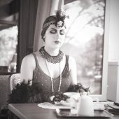 picture of black tea  - Black and White Portrait of The Beautiful Retro Woman Pouring Tea from a Teapot in the Cafe in Black Lace and Accessories in Style 1920s - 1930s